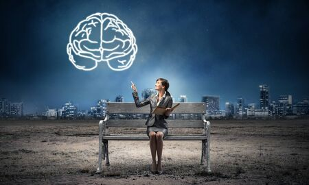 Young woman holding open book on wooden bench outdoor. Brainstorming and idea generation. Beautiful girl finger pointing at human brain symbol in night sky. Modern cityscape panorama at night.