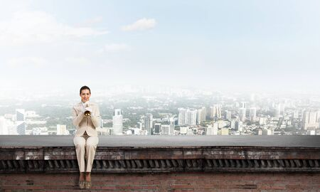 Beautiful young woman with trumpet on roof. Brave girl in white business suit with music brass instrument sitting on edge of roof. Mixed media business concept. Female musician playing music
