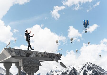 Businessman walking blindfolded on concrete bridge with huge gap as symbol of hidden threats and risks. Flying balloons and nature view on background. 3D rendering. Stockfoto