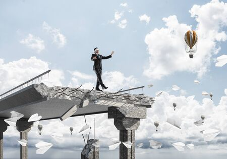 Businessman walking blindfolded among flying paper planes on concrete bridge with huge gap as symbol of hidden threats and risks. Flying balloons and nature view on background. 3D rendering. Stock Photo