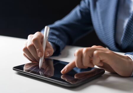 Man in business suit using digital tablet computer. Close-up of male hand holding pen and tablet device. Business man at workplace in office. Mobile smart device in business occupation. Stock Photo