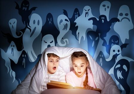 Enthusiastic little girl and boy reading book in bed after bedtime. Kids in pajamas with flashlight hiding under blanket together. Fearful children and imaginary monsters on deep blue background. Zdjęcie Seryjne