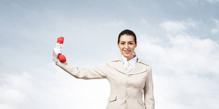 Smiling woman holds red handset phone on distance. Happy operator in business suit posing with cellphone on blue sky background. Business assistance and consultation. Customer service support concept