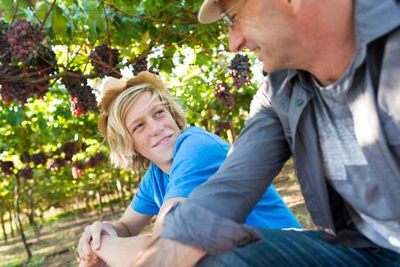 Winegrowers in straw hats relaxing in garden at sunny day. Father and son gardeners speaking and looking each other. Senior and young winemakers in their vineyard. Small family winery business Stock Photo