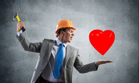Furious businessman going to crash red heart with hammer. Young handsome man in business suit and safety helmet standing on grey wall background. Love treason and crisis in family relationships.