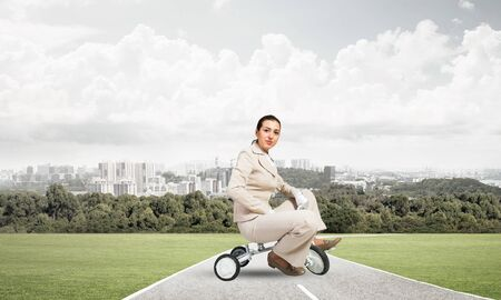 Beautiful young woman riding childrens bicycle on asphalt road. Businesslady in white business suit cycling small bike outdoor. Modern city on horizon. Professional career start concept.