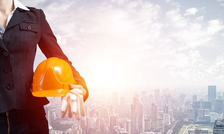 Mujer arquitecto con casco de seguridad y guantes de goma en la mano. Supervisora sobre antecedentes de la metrópoli moderna. Gestión de proyectos de ingeniería y construcción industrial. Desarrollo de carrera