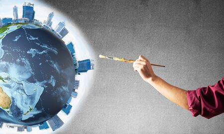 Close up artist hand drawing earth globe. Male painter in dirty shirt and bandana with paintbrush on grey wall background. Creative hobby and artistic occupation. World ecology and environment concept