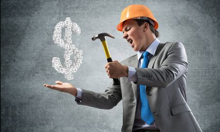 Furious businessman going to crash with hammer dollar symbol. Young handsome man in business suit and safety helmet standing on wall background. Financial crisis, bankruptcy and inflation pressure. Banco de Imagens