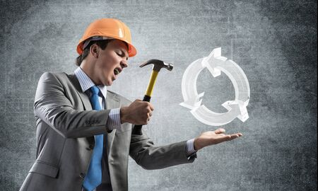 Furious businessman going to crash glass recycle sign with hammer. Young handsome man in business suit and safety helmet standing on wall background. Ecology and renewable resources process.