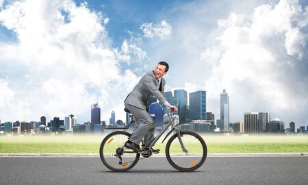 Businessman commuting to work by bike. Man wearing business suit riding bicycle on asphalt road. Handsome cyclist looking back on background of modern cityscape and blue cloudy sky.