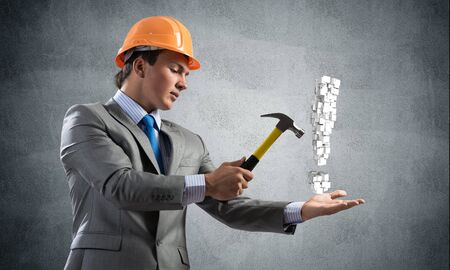 Businessman going to crash with hammer exclamation mark. Young handsome man in business suit and safety helmet standing on wall background. Search for solution and realization. Risk management