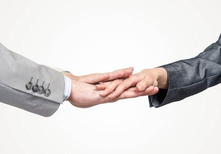 Cerca de empresarios juntando sus manos contra el fondo blanco.