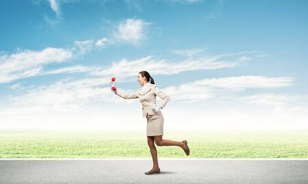 Woman running outdoor with vintage red phone. Call center operator in white business suit with telephone on road. Hotline telemarketing and communication. Professional business assistance and support Banco de Imagens