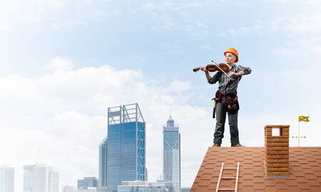 Beautiful young woman musician in safety helmet playing violin. Female builder in checkered blue shirt with instruments standing on brick roof of building. Renovation and roofing construction.