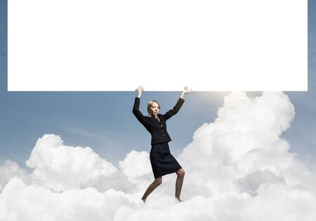 Beautiful woman in suit holding overhead big white banner. Blank whiteboard template with copy space for message. Businesswoman something presentation and promotion. Business advertising and marketing