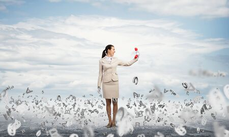 Woman standing outdoor with red phone. Elegant secretary with telephone and flying various letters around. Business assistance and support concept with copy space. Information flows and management