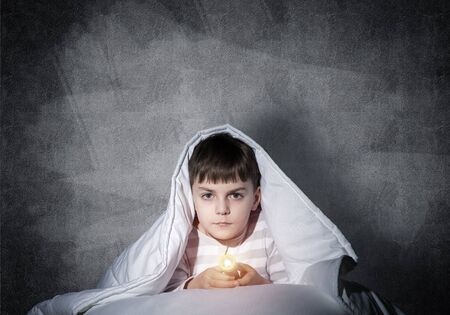 Serious child with flashlight hiding under blanket. Attentive kid lying in his bed at home. Fear to sleep in darkness at night. Portrait of little boy in pajamas on background of grey wall. Reklamní fotografie
