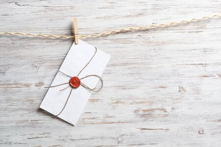 White classic envelope hanging on twine rope with clothespins. Vintage declaration of love on wooden painted background. Retro letter envelope with sealing wax stamp. Romantic wedding invitation. Stock Photo
