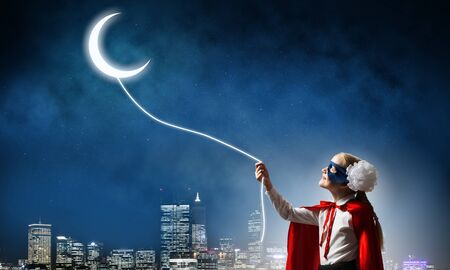 Kid girl in mask and cape catching moon in sky