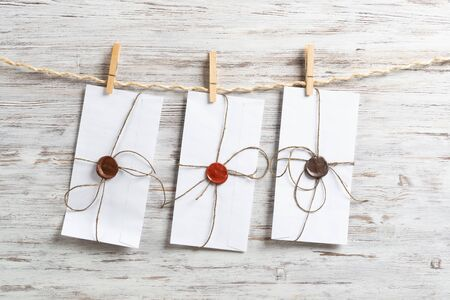 White envelopes hanging on rope on wooden background. Vintage declaration of love. Twine rope with wooden clothespins. Letter envelope with wax seal stamp. Anniversary invitation layout.