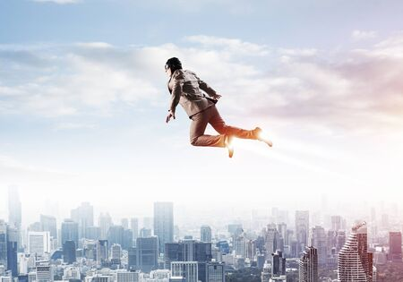 Businessman in suit and aviator hat flying in blue sky as superhero Stock Photo