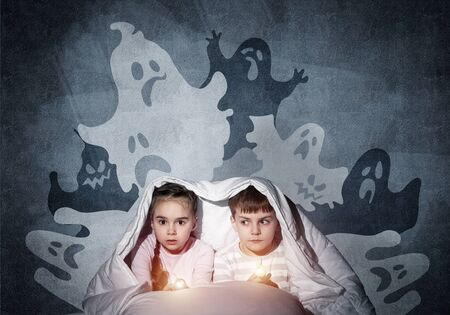 Scared girl and boy reading kids book in bed. Frightened children lying under blanket together. Kids in pajamas and funny ghosts silhouettes back on grey wall. Children reading magic fairy tales