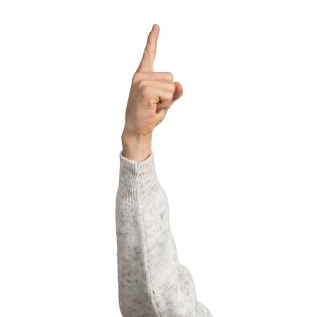 Man hand in white sweater showing finger pointing gesture with forefinger. Human hand gesturing sign isolated on white background studio shot. Male raised arm presenting popular gesture.