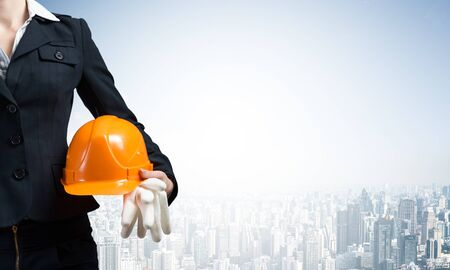 Woman architect holding safety helmet and rubber gloves in hand. Female supervisor on background of modern metropolis. Industrial engineering and construction project management. Career development