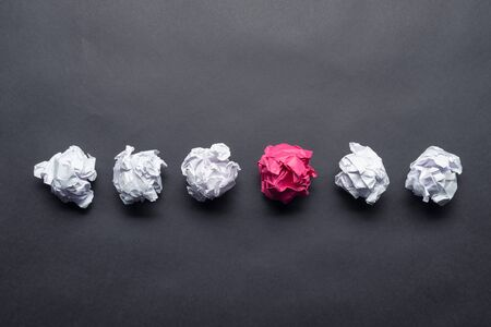 Crumpled pink paper ball among white balls on black background. Extraordinary solution of problem. Business motivation with copy space. Unique and different experience. Idea generation and imagination Banco de Imagens