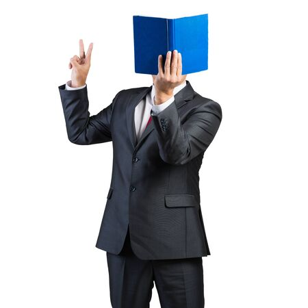 Businessman covered his face with book and finger pointing up. Portrait of man in business suit and tie standing on white background. Education and professional knowledges. Reference information. Imagens