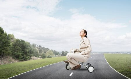 Caucasian woman riding kids bicycle on asphalt road. Young employee in white business suit biking outdoor. metaphor of ineffective and incompetent work. Beginner level concept with bicyclist.