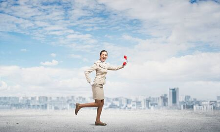 Woman running outdoor with vintage red phone. Expressive secretary in white business suit with telephone on road. Hotline telemarketing and communication. Professional business assistance and support Banco de Imagens
