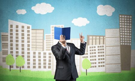 Businessman covered his face with organizer and showing fingers victory sign. Man in business suit standing on cityscape illustration background. Education and knowledges. Direction and instruction. Standard-Bild - 134607864