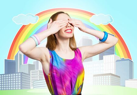 Redhead beautiful woman with hands covering eyes. Elegant lady in bright dress and bracelets. Flirty girl posing on background cartoon city with rainbow. Young woman waiting for pleasant surprise.