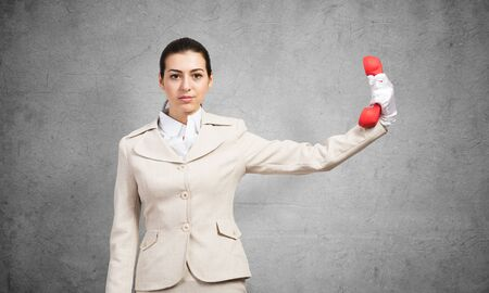 Woman keep at distance vintage red phone. Elegant operator in white business suit posing with landline phone in hand. Hotline telemarketing and business communication. Business assistance and support