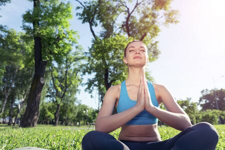 Girl meditates in lotus pose on green grass at sunrise. Practicing of yoga. Portrait of young woman with closed eyes. Training and meditation outdoor at summer day. Healthy lifestyle and relaxation.