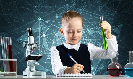 Little girl scientist with test tube writing in notebook. Research and education in school. Chemical laboratory with microscope and glass flasks. Schoolgirl making experiment in chemistry class. Stock Photo