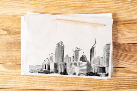 Modern megapolis skyline pencil draw. Urban architecture with high skyscrapers sketch on wooden surface. Sheet of paper on textured natural wooden background. Creative cityscape painting.