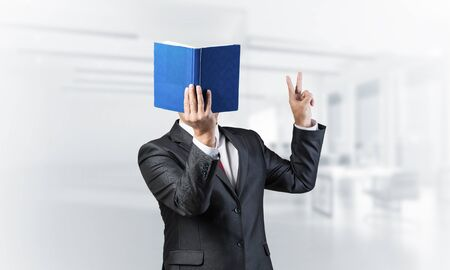 Businessman covered his face with book and finger pointing up. Portrait of man in business suit standing in blurred office interior. Education and professional knowledges. Reference information.
