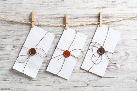 White classic envelopes hanging on twine rope with clothespins. Vintage declaration of love on wooden painted background. Retro letter envelope with sealing wax stamp. Romantic wedding invitation. Archivio Fotografico