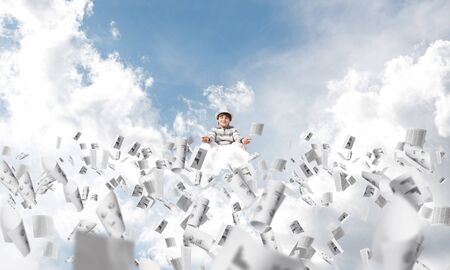Young little boy keeping eyes closed and looking concentrated while meditating among flying papers in the air with cloudy skyscape on background.