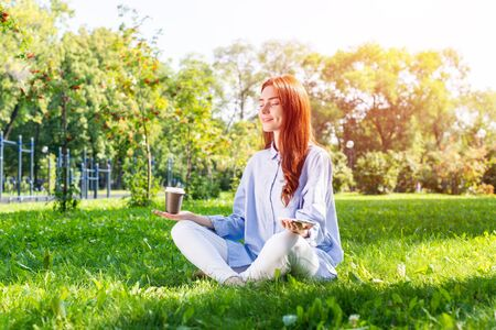 Young redhead woman meditating in lotus pose with cup of coffee on green grass. Beautiful calm girl in casual wear practicing of yoga with closed eyes in park. Mental relax and balance concept.
