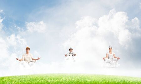 Young family keeping eyes closed and looking concentrated while meditating on clouds in the air with bright and beautiful landscape on background.