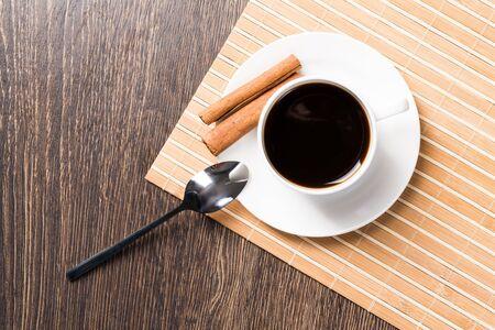 Tasse Espressokaffee auf Holztisch. Draufsicht weiße Porzellantasse und Zimtstangen auf Untertasse. Frisches und aromatisches Heißgetränk im Café hautnah. Morgenkaffee und Pausenzeitkonzept.
