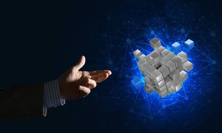 Close of businessman hand holding cube figure as symbol of innovation, mixed media Stockfoto