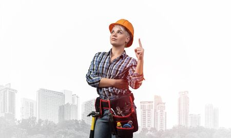 Beautiful female builder in hardhat with finger pointing upward. Portrait of smiling young woman in checkered blue shirt standing on foggy downtown background. Industrial architecture and construction