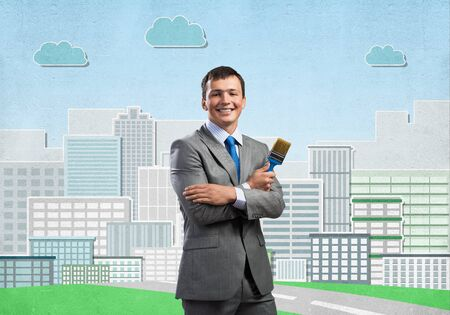 Confident and creative businessman painter standing with arms folded. Happy handsome man in business suit and tie holding paintbrush on background cityscape illustration. Creativity in business. Stock fotó