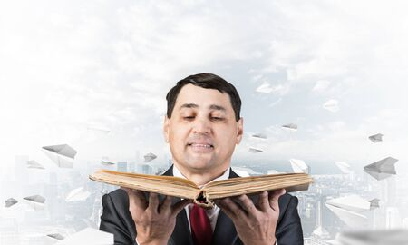 Happy businessman holding open old book. Smiling man in suit standing on downtown background with flying paper planes. Lawyer holding big legal regulation book. Business accounting and consulting