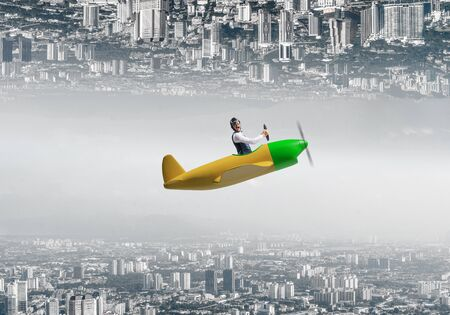 Businessman flying in small airplane. Two modern urban worlds located upside down to each other. Funny man in aviator hat and goggles driving propeller plane. Business center with skyscrapers
